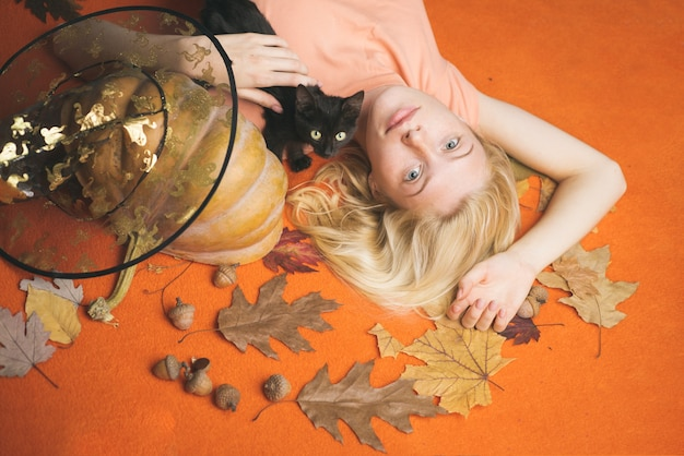 Portrait of gorgeous blonde witch and hat with pumpkin over orange background. wide halloween party art design. beautiful young woman in black witch costume with hat over orange background.
