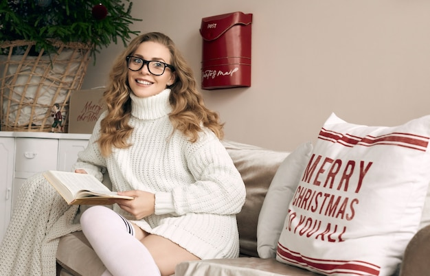 Portrait of gorgeous blonde woman in white woolen sweater and glasses reading book in light cozy decorated interior