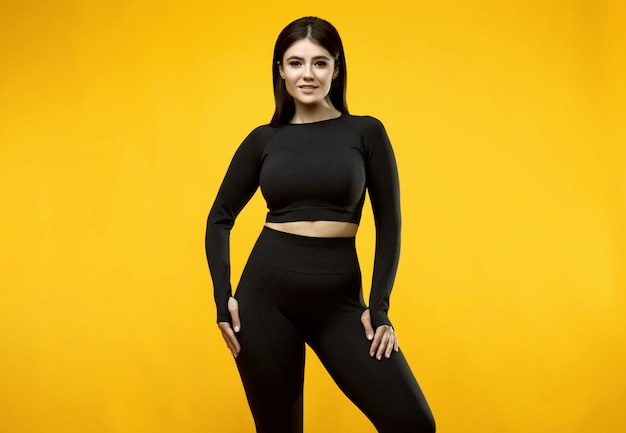 Portrait of a gorgeous body positive latin woman in a black sports suit posing on yellow