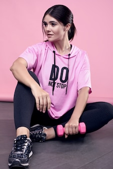 Portrait of a gorgeous body positive latin woman in a pink sports hoodie exercising with dumbbells on pink