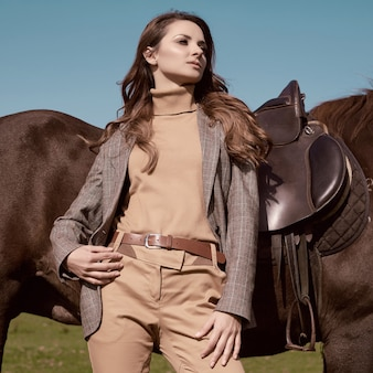 Portrait of a gorgeous brunette woman in an elegant checkered brown jacket posing with a horse on country landscape