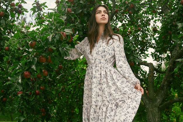 Portrait of gorgeous brunette woman in fashion classic dress posing among an apple trees