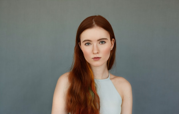 Portrait of gorgeous caucasian female with long red hair standing isolated at blank grey wall, having serious look, staring. young woman looking defenseless. youth, beauty and fashion