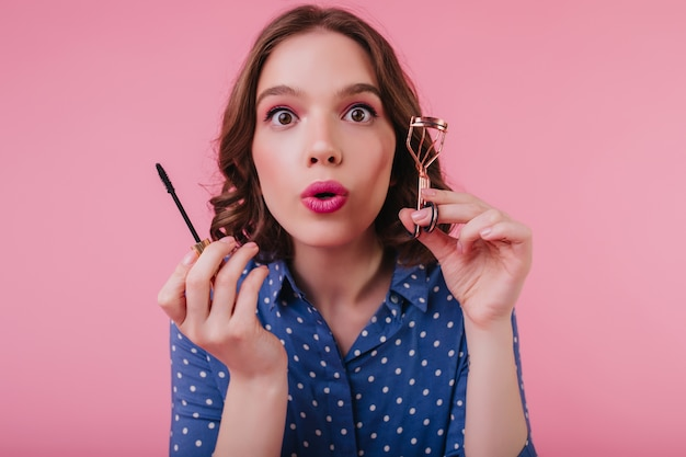 Portrait of gorgeous dark-eyed lady with short hairstyle curls her eyelashes. romantic surprised girl holding mascara brush and doing makeup.
