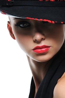 Ritratto di donna splendida con labbra rosso brillante e cappello alla moda