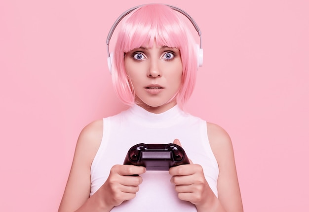 Portrait of gorgeous happy gamer girl with pink hair playing video games using joystick on colorful in studio