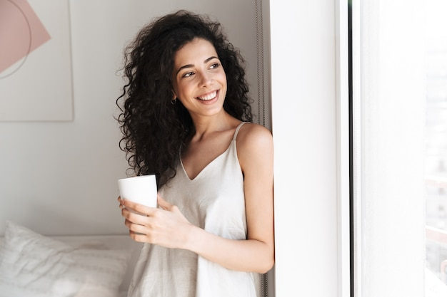 Portrait of gorgeous happy woman with long curly hair looking aside through window in morning at home, and holding cup of tea