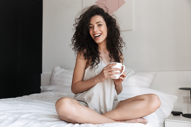 Portrait of gorgeous happy woman with long curly hair sitting on bed with white clean linen at home in morning, and holding cup of tea