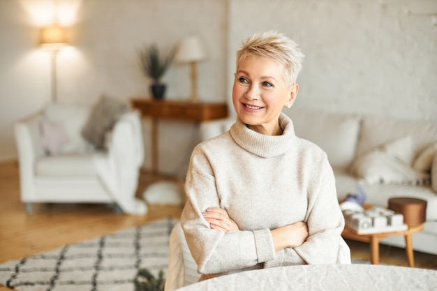 Portrait of gorgeous mature european female with short hairstyle relaxing at home sitting at table in living room crossing arms on chest trying to warm up in cozy cashmere turtleneck sweater, smiling
