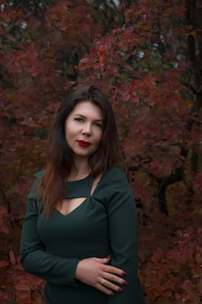 Portrait of a gorgeous middle-aged woman in an autumn park. hello november. stylish adult woman in a beautiful dress
