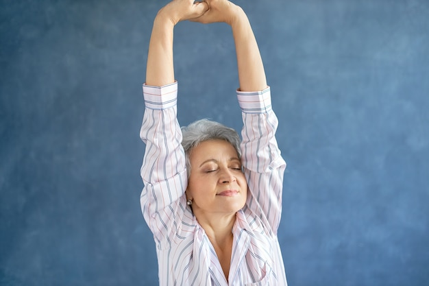 Portrait of gorgeous middle aged woman in stylish striped pajamas stretching body after awakening early in the morning
