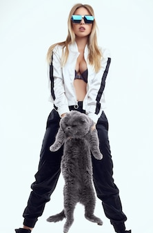 Portrait of gorgeous model girl in a tracksuit posing with a fat pedigree cat isolated