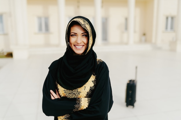 Portrait of gorgeous muslim woman with toothy smile and arms crossed standing. in background luggage.