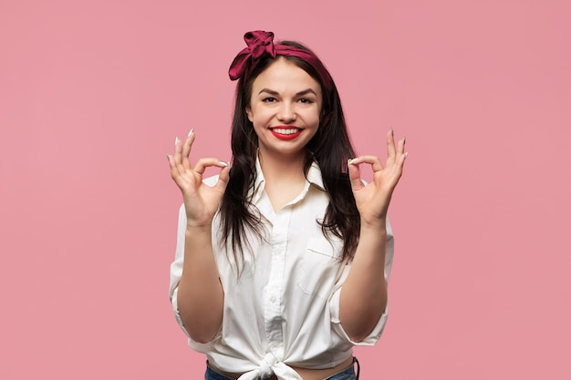 Portrait of gorgeous pin up girl wearing white shirt and red headscarf making approving gesture with both hands