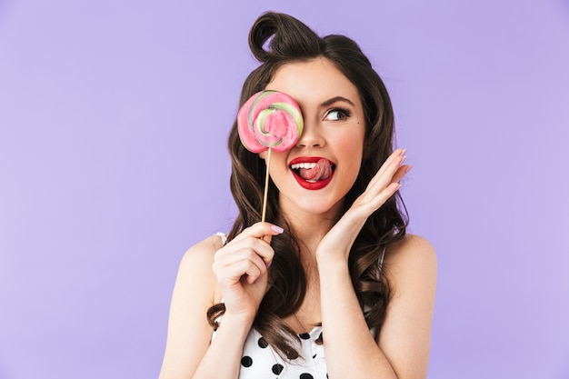 Portrait of gorgeous pin-up woman in vintage polka dot dress smiling while holding and eating colorful lollipop isolated over violet wall