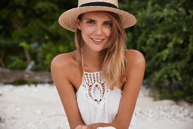 Portrait of gorgeous relaxed female model wears summer straw hat and white dress, has good rest alone outdoor, breathes fresh air and admires sunshine. people, season and recreation concept.