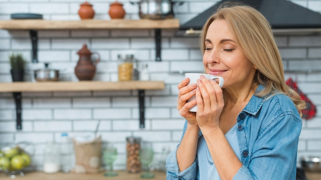 Portrait of gorgeous smiling lady smelling and drinking coffee from cup in the kitchen