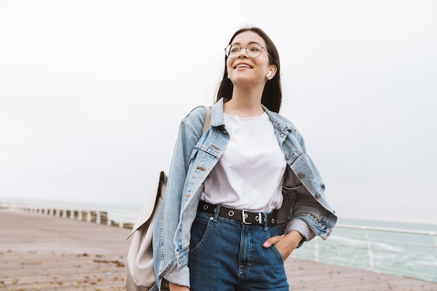 Portrait of gorgeous teenage girl wearing earpods and eyeglasses smiling while walking along wooden pier by seaside