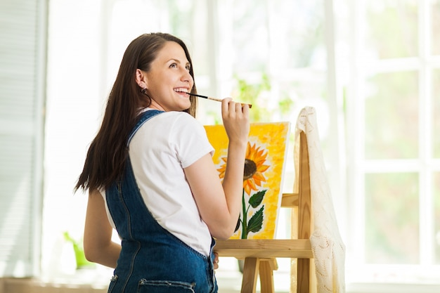 Portrait of gorgeous woman artist  painting at home