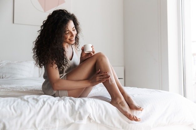 Portrait of gorgeous woman with long curly hair sitting on bed with white clean linen at bedroom, and applying body cream on her legs