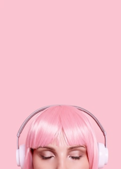 Portrait of gorgeous woman with pink hair enjoys the music in headphones