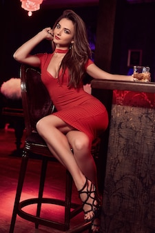 Portrait of gorgeous young brunette woman in red dress sitting at the bar