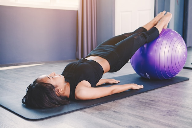 Portrait of gorgeous young woman practicing yoga indoor with ball