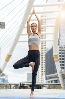 Portrait of gorgeous young woman practicing yoga outdoor in city.