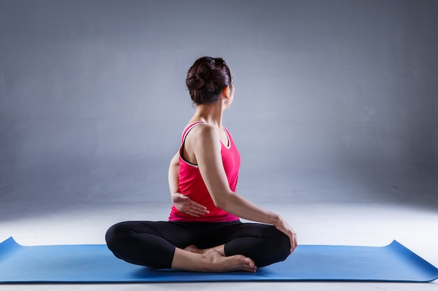 Portrait of gorgeous young woman practicing yoga in studio with on dark background