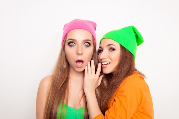 Portrait of gossip woman telling news to her shocked girlfriend