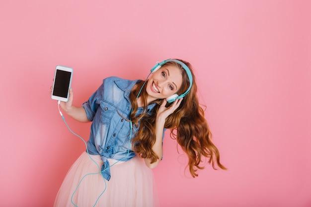 Ritratto di graziosa ragazza felice in grandi auricolari ballare e divertirsi isolato su sfondo rosa. affascinante giovane donna carina in gonna con capelli ricci che fluttuano, tenendo il telefono gode della canzone preferita