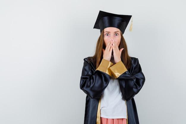Ritratto di donna laureata tenendo le mani sulla bocca in abiti casual, uniforme e guardando scioccato vista frontale