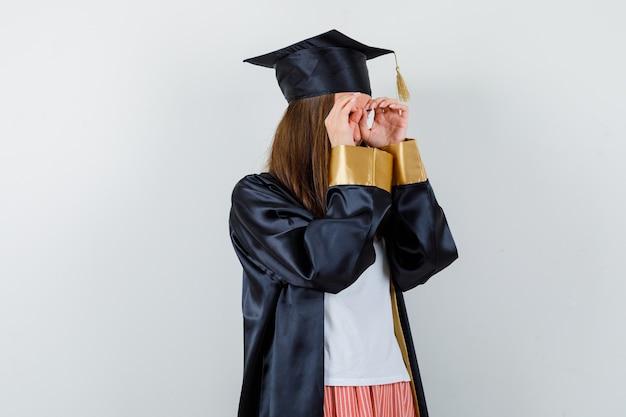 Ritratto di donna laureata che mostra il gesto di occhiali in abbigliamento casual, uniforme e guardando la vista frontale focalizzata