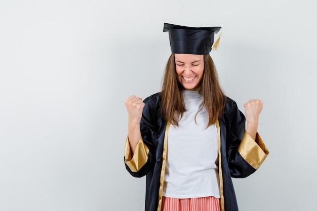 Ritratto di donna laureata che mostra il gesto del vincitore in abbigliamento casual, uniforme e che sembra felice vista frontale