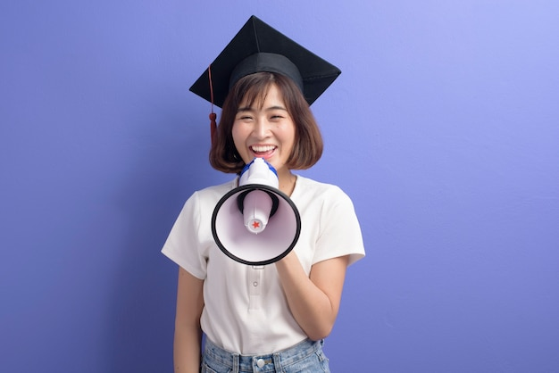 A portrait of graduated asian student holding megaphone isolated purple