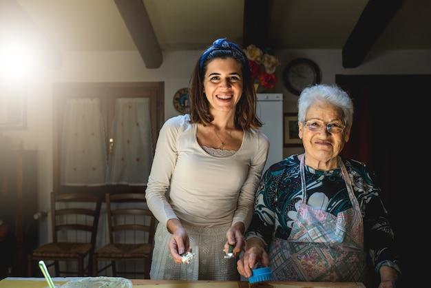 肖像画の孫娘と祖母は、検疫中に自宅で一緒に時間を過ごすことができます。手作りパスタとして伝統料理を作る。