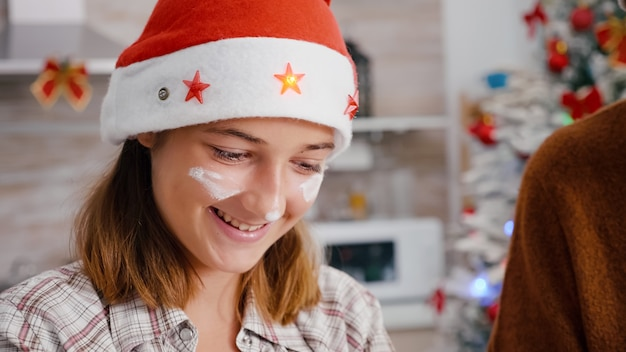 Portrait of granddaughter with flour on face wearing santa hat cooking delicious dessert