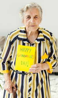 Portrait of grandmother holding greeting message