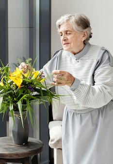 Portrait of grandmother touching flowers