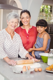 Portrait of grandmother with family making bread