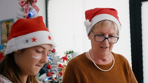 Portrait of grandmother with granddaughter wearing santa hats