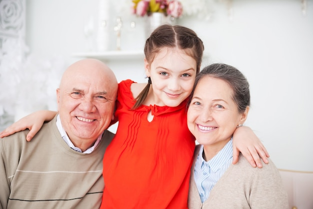 Portrait of grandparents with their granddaughter.