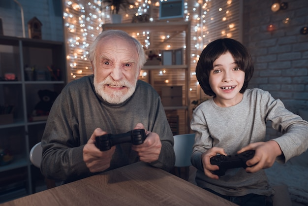 Portrait grandson play video game with grandfather