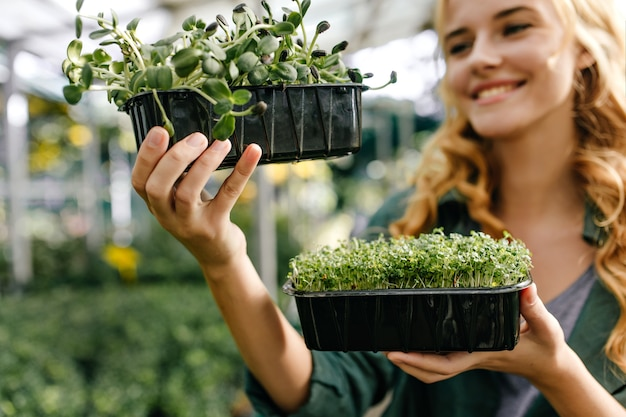 Portrait of grass in pots close-up. cheerful girl with fiery red curls shows grown manually plants.