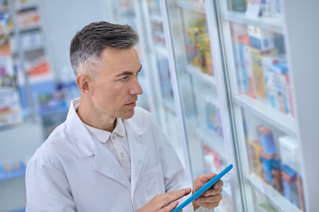 Portrait of a gray-haired male druggist with a tablet computer standing before the pharmacy display cabinet