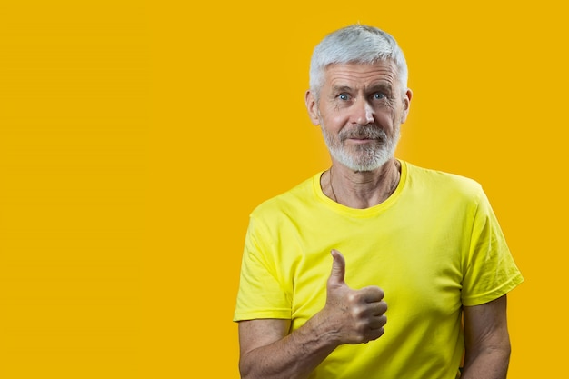 Portrait of a gray-haired man with a beard shows gesture good on blue background