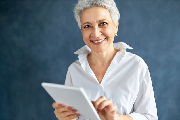 Portrait of gray haired middle aged female designer working remotely using wireless connection on digital tablet
