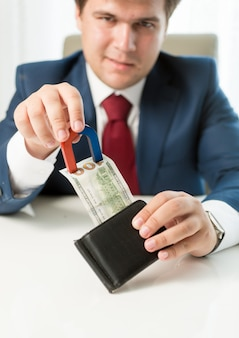 Portrait of greedy businessman pulling money out wallet with use of magnet