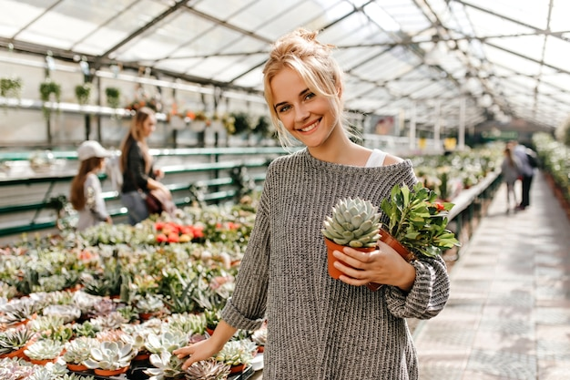 Portrait of green-eyed blonde woman in oversized sweater with smile. woman posing in greenhouse and holding succulent.