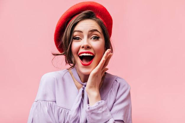 Ritratto di donna riccia dagli occhi verdi con rossetto rosso. ragazza in berretto rosso con gioiosa sorpresa guarda nella telecamera.